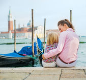 Mother and daughter sitting near gondolas in Venice — Stock Photo