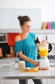 Woman in workout gear listening to music making smoothie — Stock Photo