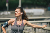 Woman runner taking a break in the sunshine listening to music — Stock Photo