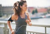 Jogging woman on bridge listening to music — Stock Photo