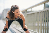 Woman jogger stretching on bridge while listening to music — Stock Photo