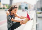 Woman runner stretching leg on rail in summer in urban setting — Stock Photo