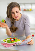 Young woman eating greek salad in kitchen and reading magazine — Stock Photo