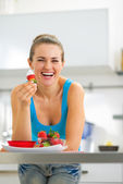 Happy young woman eating strawberry with yogurt in kitchen — Stock Photo