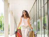 Jovem mulher com sacos de compras, andando sobre o beco shopping — Fotografia Stock