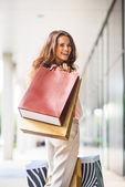 Retrato de mulher jovem feliz com sacos de compras — Fotografia Stock
