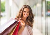 Retrato de mulher jovem sorridente com sacos de compras — Fotografia Stock