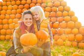 Portrait of happy mother and child holding pumpkins — Stock Photo