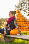Smiling young woman sitting with pumpkin in front of pumpkin pir — Stock Photo