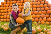 Portrait of happy mother and child choosing pumpkins — Stock Photo