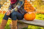 Closeup on happy young woman sitting with pumpkin in front of pu — Stock Photo