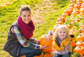 Portrait of happy mother and child among pumpkin — Stock Photo