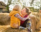 Portrait of happy mother and child kissing while sitting on hays — Stock Photo