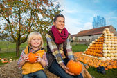 Happy mother and child sitting on haystack with pumpkins — Stockfoto