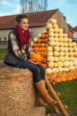 Portrait of young woman sitting on haystack with pumpkin — Stock Photo