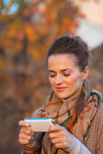 Portrait of young woman in autumn evening outdoors writing sms — Foto Stock