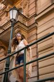 Longhaired hippy girl with sunglasses stands near old town stree — Stock Photo