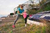 Mother helping daughter stretch on the beach using upturned boat — Stock Photo