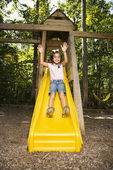 Hispanic girl sliding down outdoor — Stock Photo