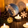 Christmas tree decorations and candles on an old wooden backgrou — Stock Photo #59771547