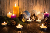 Christmas tree decorations and candles on an old wooden backgrou — Stock Photo