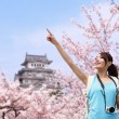 Happy travel woman with sakura tree — Stock Photo #61277187