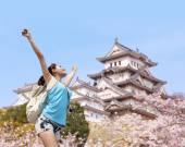 Happy travel woman with sakura tree — Stock Photo
