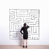 Woman looking at hand drawn maze — Stockfoto