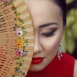 Beautiful asian female portrait with red dress and lips sitting on the green floral background holding wooden fan with flower pattern near her face — Stock Photo #62342651