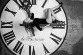 Slim beautiful female on the giant clock — Стоковое фото