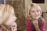 Child looking in mirror at missing front tooth — Stock Photo