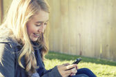 Teenage girl smiling while using a cell phone — Stock Photo