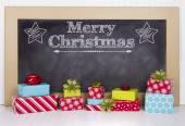 Christmas presents grouped around a chalkboard — Stock Photo