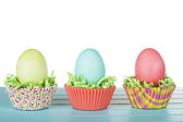 Dyed Easter eggs in a nest of green grass confetti and cup cake — Stock Photo