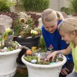 Two young girls helping to make fairy garden in a flower pot — Stock Photo #74264745