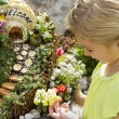Child looking at fairy garden in a flower pot outdoors — Stock Photo #74264783