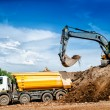 Industrial truck loader excavator and bulldozer moving earth and unloading into a dumper truck — Stock Photo #51826657