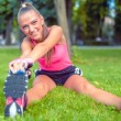 Blonde smiling beautiful woman stretching and warming up for fitness training in park — Stock Photo