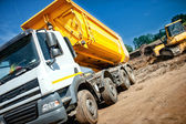 Dumper truck at industrial constrution site waiting for the earth load from excavator — Stock Photo