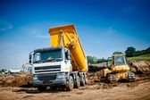 Dumper truck and bulldozer at highway road construction site — Stock Photo