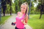 Beautiful woman running in park and listening to music while stretching — Stock Photo