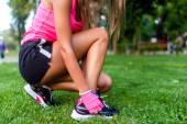 Close-up of active jogging female runner, preparing shoes for training and working out at fitness park — Stock Photo