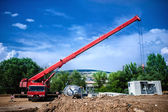Industrial Crane operating and lifting an electric generator and concrete mobile station against sunlight and blue sky — Stock Photo