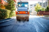 Road repairing in urban modern city with heavy vibration roller compactor — Stock Photo