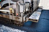 Pavement machine laying fresh asphalt or bitumen on top of the gravel base during highway construction or road repairing — Stock Photo
