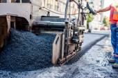 Worker or engineer operating an asphalt paving machine at road construction — Stock Photo