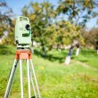 Total station surveying and measuring engineering equipment at work in garden or forest — Stock Photo