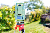 Surveying equipment with transit total station and theodolite with garden background — Stok fotoğraf