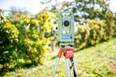 Surveyor engineering equipment with theodolite and total station in a garden at a construction site — Stok fotoğraf