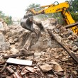 Industrial excavator and bulldozer loading debris and demolition concrete walls into a container — Stock Photo #56066715